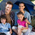 Happy family on a camping trip in their tent on a sunny day